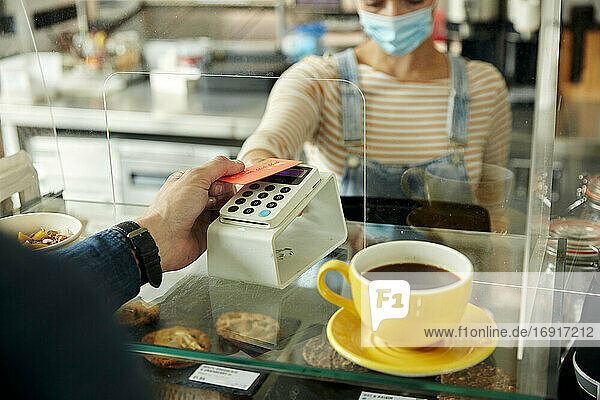 Woman in a face mask behind cafe safety screen  offering a contactless payment terminal to customer