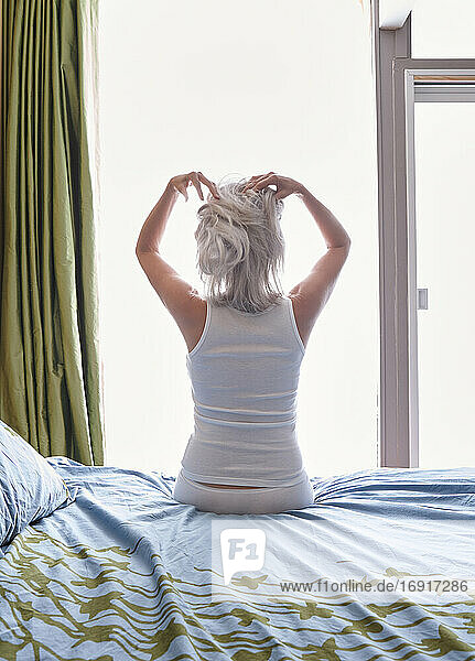 Mature woman in her bedroom sitting on her bed massaging her head with her fingers