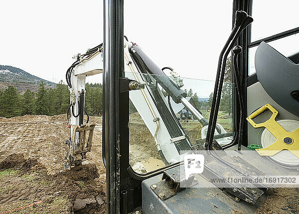 Mechanical digger excavating ground in rural environment.