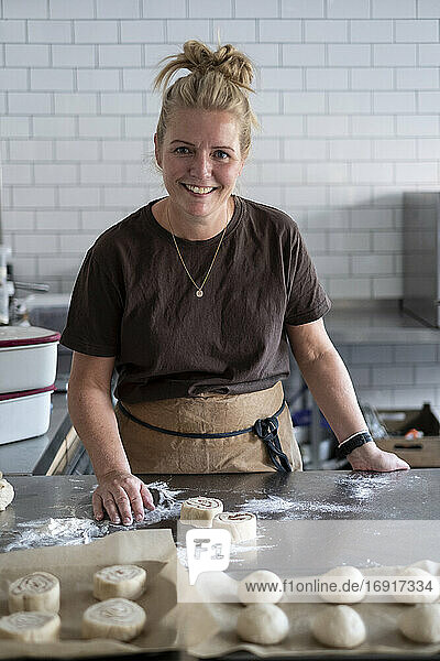 Woman working in a kitchen  preparing danish pastries dough.