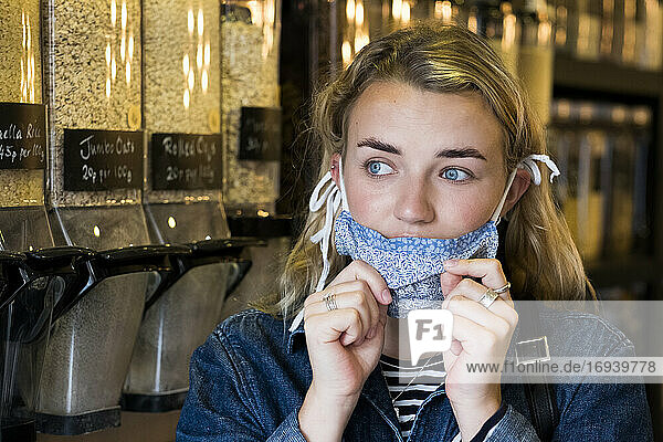 Young blond woman wearing face mask  shopping in waste free wholefood store.