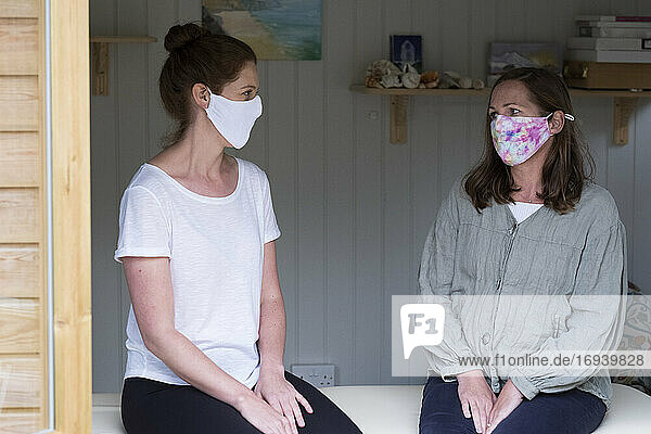 Woman and female therapist wearing masks  at a therapy session