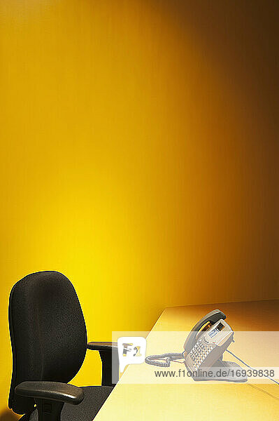 Desk with chair and telephone and yellow wall behind.