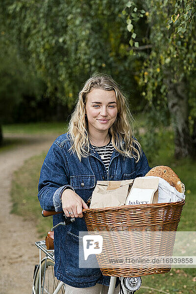 Young blond woman on bicycle with basket  smiling at camera.