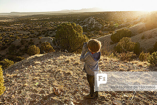 young boy in Galisteo Basin looking through binoculars at sunset