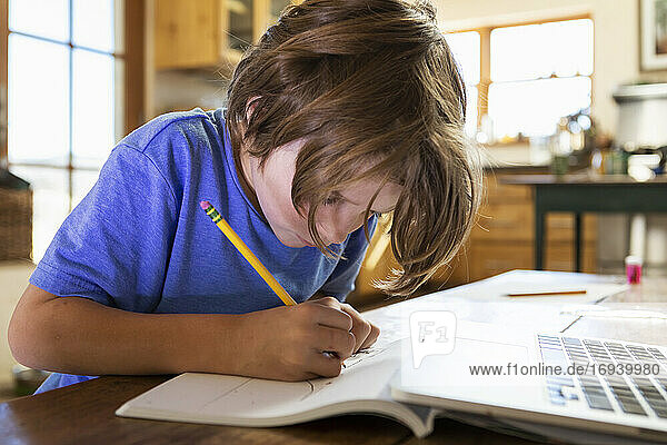 Young boy at home writing and drawing in his drawing pad