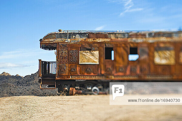 Rusty vintage train carriage in desert.