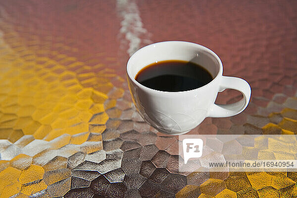Cup of black coffee on glass table.