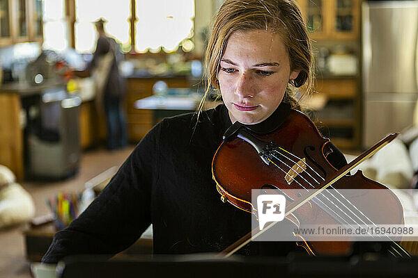 Teenager-Mädchen übt Geige zu Hause