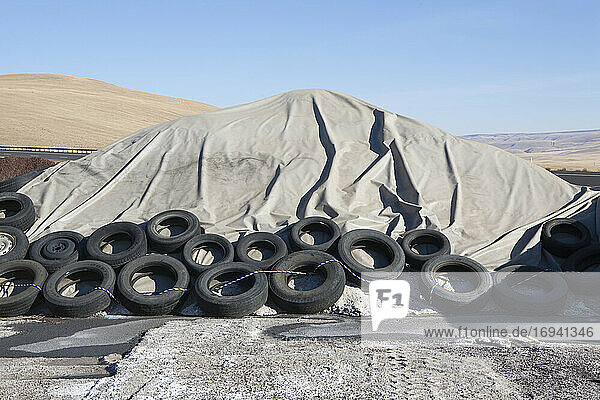 Heap of waste covered with tarpaulin  weighted down by rubber tires.