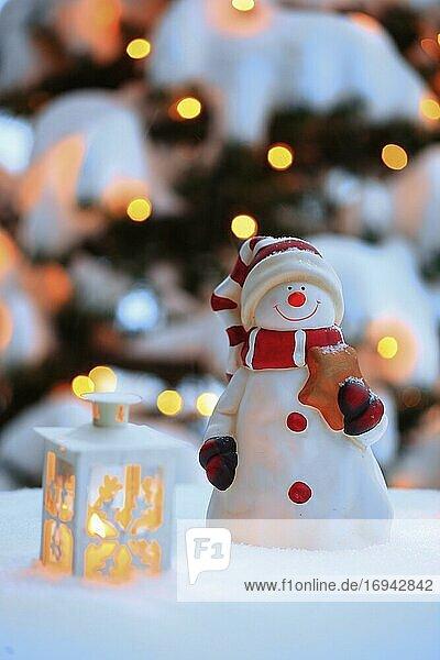 Stimmungsvolle Weihnachtsdekoration im Freien mit Schneemann  Laternen  Schnee und Lichterkette an Weihnachtsbaum