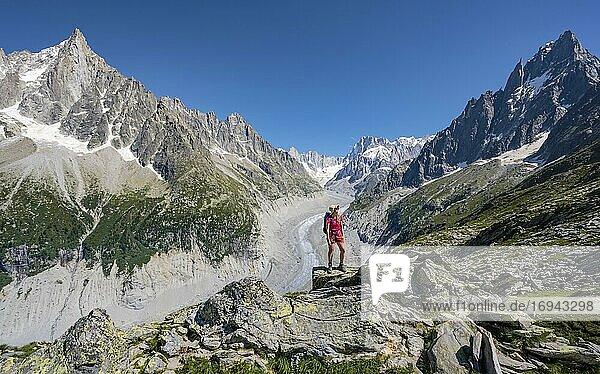 Bergsteigerin steht auf Felsen  Grand Balcon Nord  Gletscherzunge Mer de Glace  hinten Grandes Jorasses  Mont-Blanc-Massiv  Chamonix  Frankreich  Europa