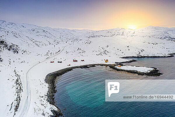 Verschneite Straße zum Fischerdorf Breivikbotn bei Sonnenuntergang  Insel Soroya  Hasvik  Troms og Finnmark  Nordnorwegen  Skandinavien  Europa