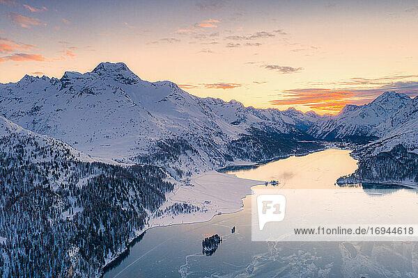 Luftaufnahme des Sonnenuntergangs über dem Silsersee und dem schneebedeckten Piz Da La Margna  Malojapass  Engadin  Kanton Graubünden  Schweizer Alpen  Schweiz  Europa