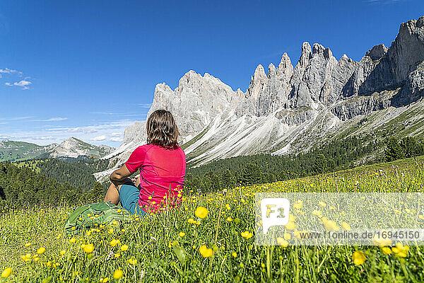 Junge Frau bewundert die Geiselspitzen auf den blühenden Wiesen der Malga Brogles  Val di Funes  Südtirol  Dolomiten  Italien  Europa