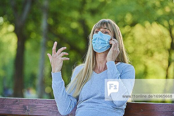 Frau mit Mundschutzmaske telefoniert in einem Stadtpark  Corona-Krise  Regensburg  Bayern  Deutschland