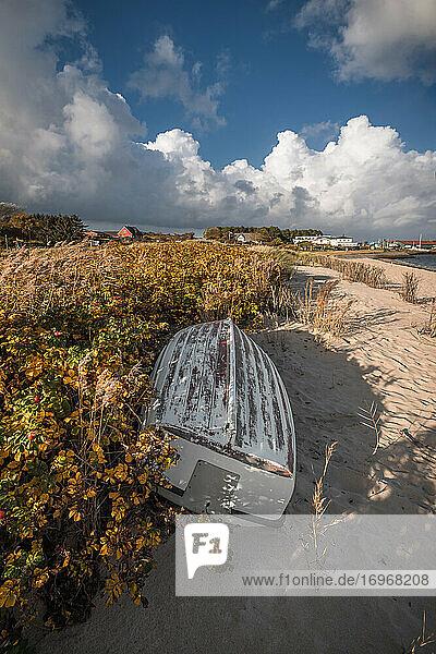 Altes Boot liegt kieloben am Strand von Munkmarsch/Sylt im herbstlichen Sonnenschein. Im Hintergrund der Hafen und das Fährhaus Munkmarsch