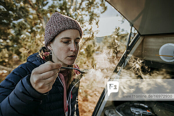 woman blows hot steaming spoonful of soup while camping with camper