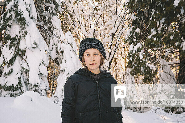 Young Boy in Beanie Stands in a Snowy Scene.