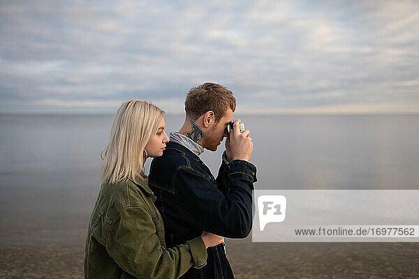 Junges Paar beim Fotografieren von Wasser in der Natur