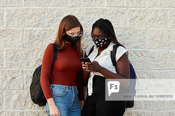 Zwei junge Frauen mit einer Maske schauen auf ihr Smartphone. Multiethnisch