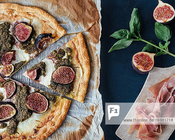 Top down view of ricotta  fig and pesto pizza with prosciutto