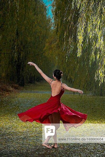 Die junge Frau im roten Rock beim Tanzballett im Freien
