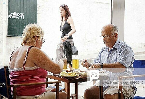 Zwei übergewichtige Menschen essen in Menorca zu Mittag. Spanien.