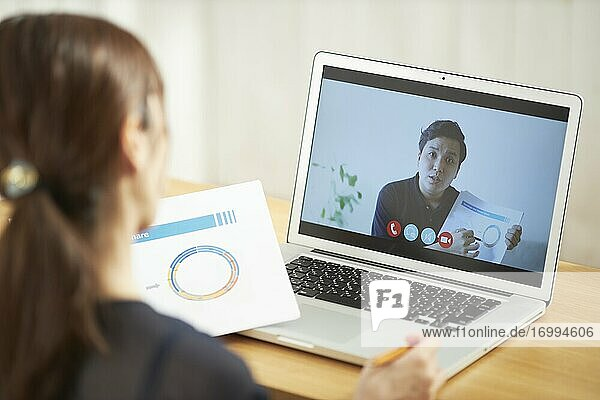 Young Japanese businesswoman having remote meeting at home