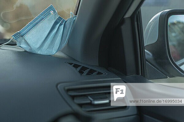 Gesichtsschutzmaske auf dem Armaturenbrett des Autos