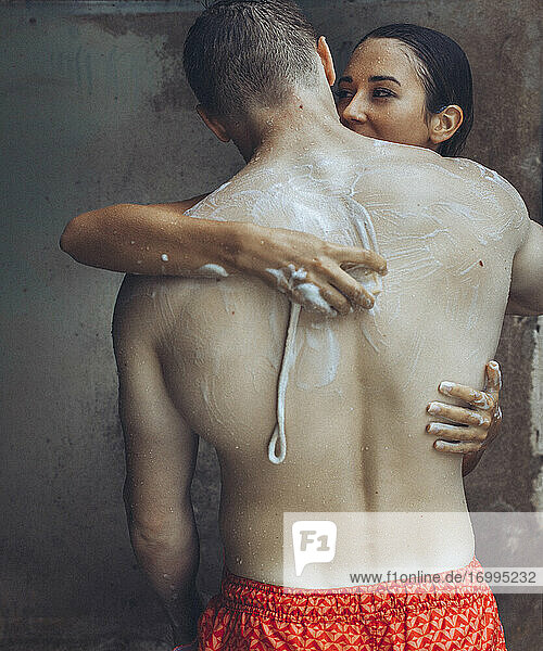 Sensual young couple with soap in outdoor shower