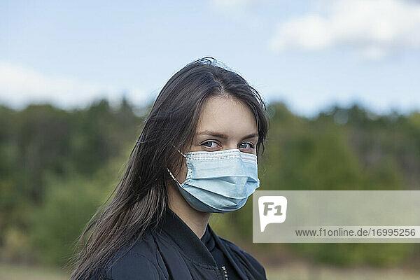 Porträt selbstbewusste junge brünette Frau in Gesichtsmaske