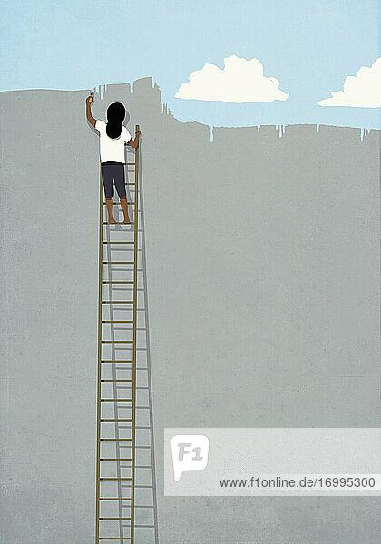 Frau auf Leiter malen blauen Himmel über graue Wand