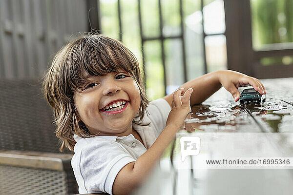 Porträt glücklich  niedlich Kleinkind Junge spielt mit Spielzeugauto auf nassen Terrassentisch