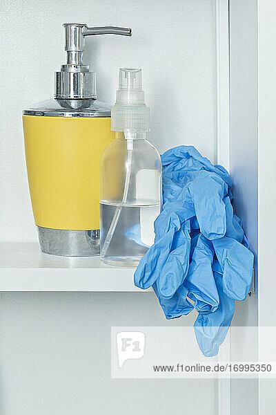 Schutzhandschuhe im Badregal mit Seife und Desinfektionsmittel