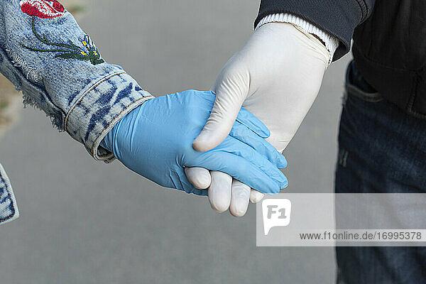 Nahaufnahme zärtliches Paar hält Hände in Gummihandschuhen