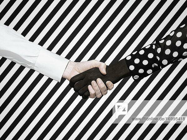 Multiethnischer Händedruck auf gestreiftem Hintergrund