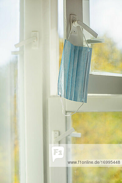 Gesichtsmaske hängt am Fensterriegel