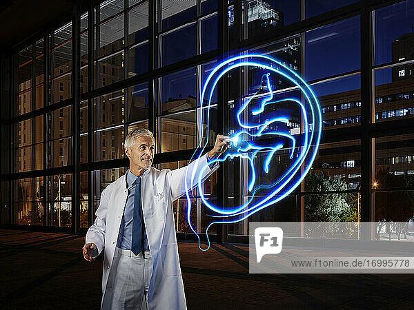 Männlicher Arzt  der eine Gebärmutter und einen Fötus mit Lichtmalerei im Labor eines Krankenhauses untersucht Männlicher Arzt, der eine Gebärmutter und einen Fötus mit Lichtmalerei im Labor eines Krankenhauses untersucht