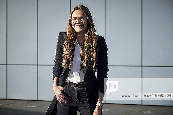 Female professional smiling while standing against wall