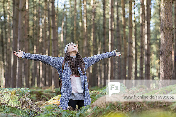 Female hiker with arms outstretched standing in Cannock Chase forest during winter