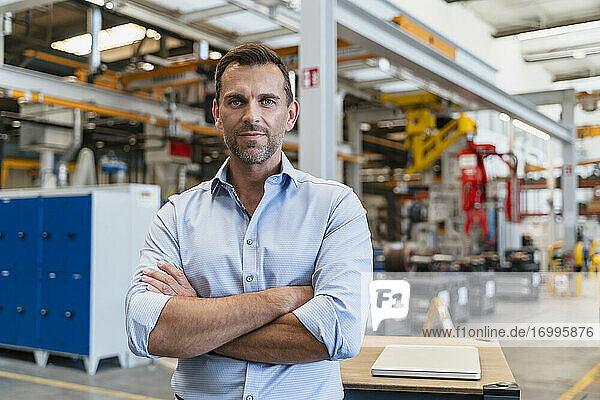 Businessman with arms crossed standing in factory