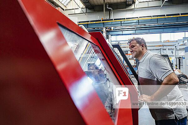 Älterer männlicher Techniker  der in einer beleuchteten Industrieanlage neben Maschinen steht und schaut