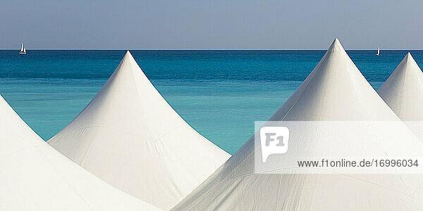 White beach tents against blue coastal water ofMediterraneanSea