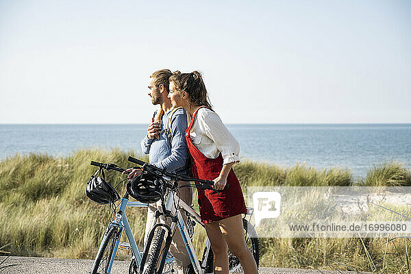 Girlfriend with arm around boyfriend admiring sea view while standing with bicycles at beach