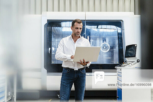 Businessman concentrating while working on laptop standing in factory