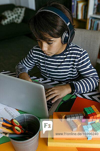 Vorpubertierender Junge benutzt Laptop während des Hausunterrichts Vorpubertierender Junge benutzt Laptop während des Hausunterrichts