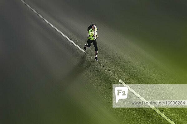 Young woman jogging along asphalt street
