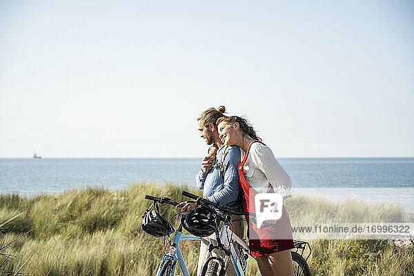 Young woman leaning on man while standing with bicycles at beach