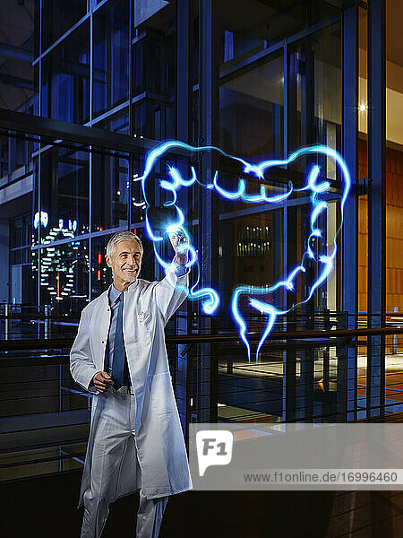 Male gastroenterologist examining large intestine with light painting at hospital
